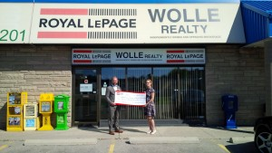 Mark Wolle, Broker of Record, Royal Le Page Wolle Realty, presents a donation cheque to Kourtney Beckman of Women's Crisis Services for $10,091 in support of Anselma House.